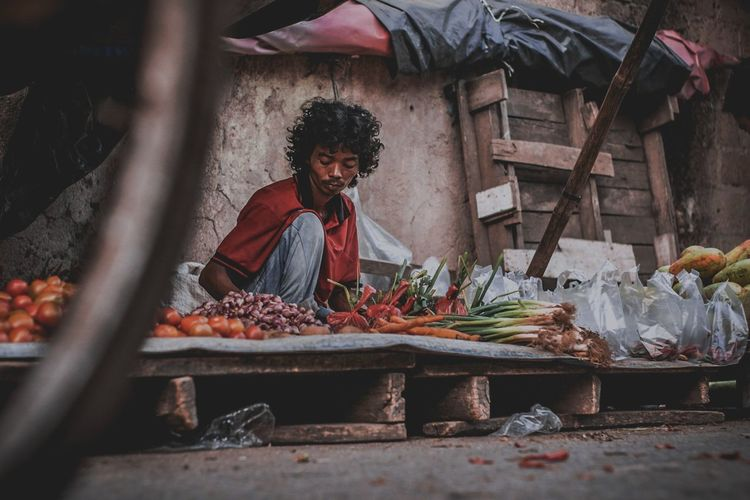 Mid adult man selling vegetables at market