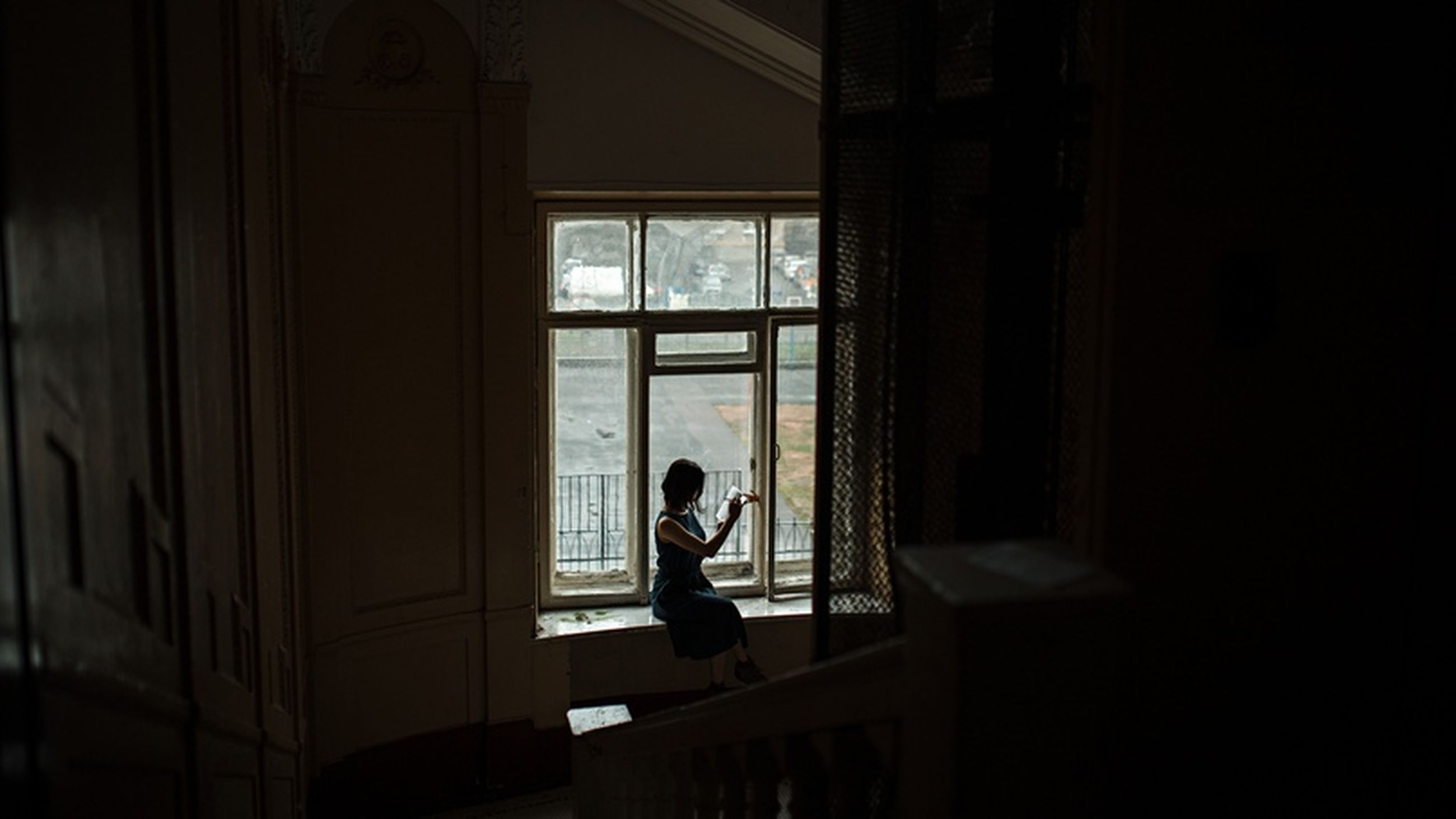 window, one person, real people, sitting, indoors, lifestyles, leisure activity, day, architecture, young adult, built structure, casual clothing, domestic room, full length, young women, women, adult, contemplation