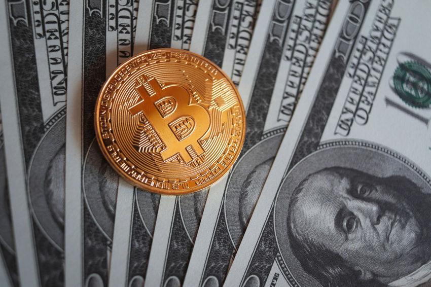 bitcoin cryptocurrency token on fanned out US $100 dollar bills Bitcoin Cryptocurrency Blockchain Encrypted Blockchain Technology Currency Crypto Money Finance Cash Wealth Banking Savings Financial Invest Investing Investment Banknote Dollars Mining Coin