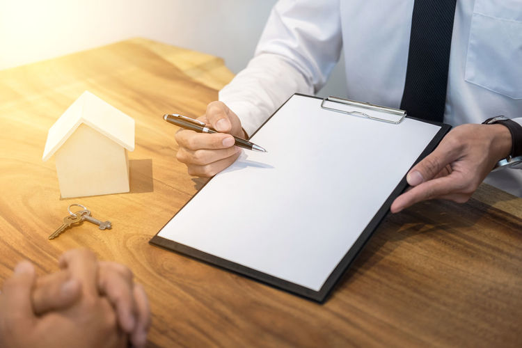 Midsection Of Male Real Estate Agent Showing Blank Paper To Costumer At Desk