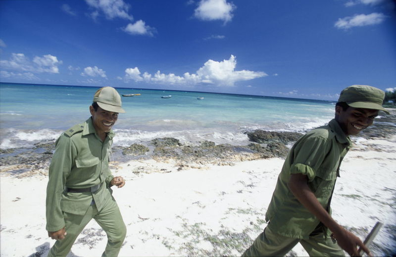 Portrait Of Smiling Security Guards Walking At Beach Against Sky