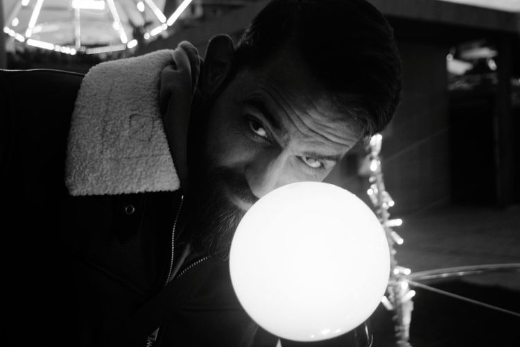 Close-up portrait of man holding illuminated lighting equipment