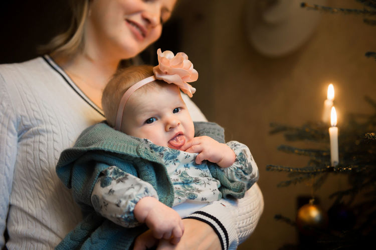 Christmas Baby Babygirl Babyhood Bonding Care Casual Clothing Childhood Christmas Tree Cute Daughter Family Family With One Child Focus On Foreground Happiness Indoors  Innocence Leisure Activity Lifestyles Love Mother Real People Smiling Togetherness Young Women