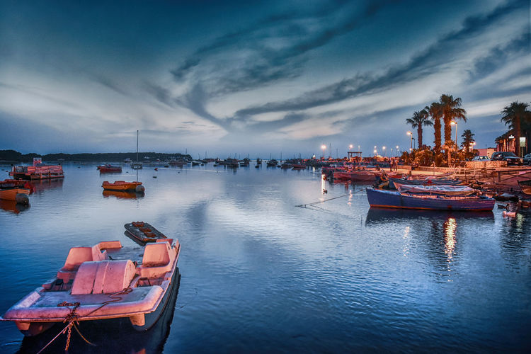 Boats moored in sea against sky at sunset