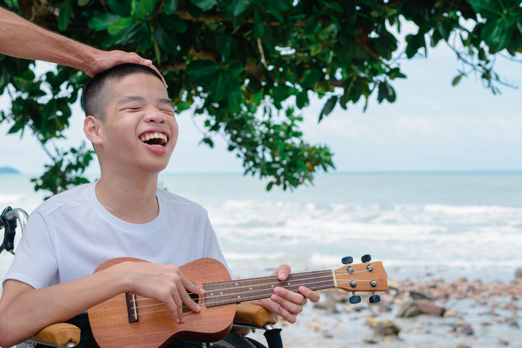 Close-up of smiling boy sitting on wheelchair and playing guitar against sea