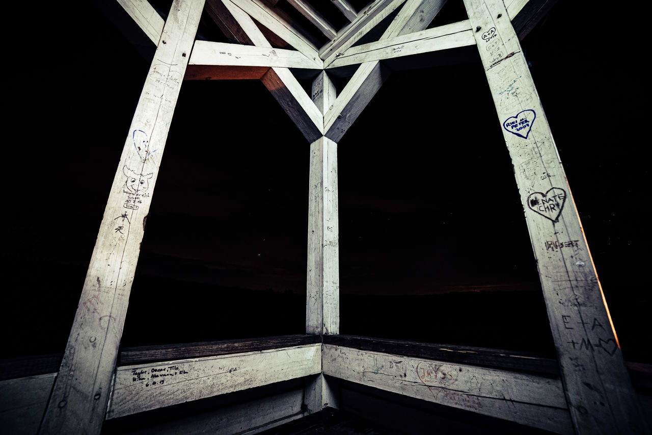 architecture, built structure, no people, low angle view, night, wood - material, metal, indoors, pattern, sky, dark, nature, communication, building, art and craft, close-up, industry, girder, underneath