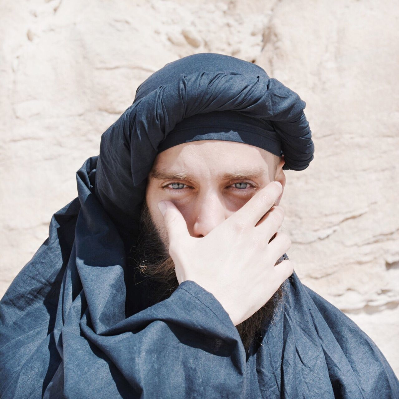 Portrait of man covering face during sunny day