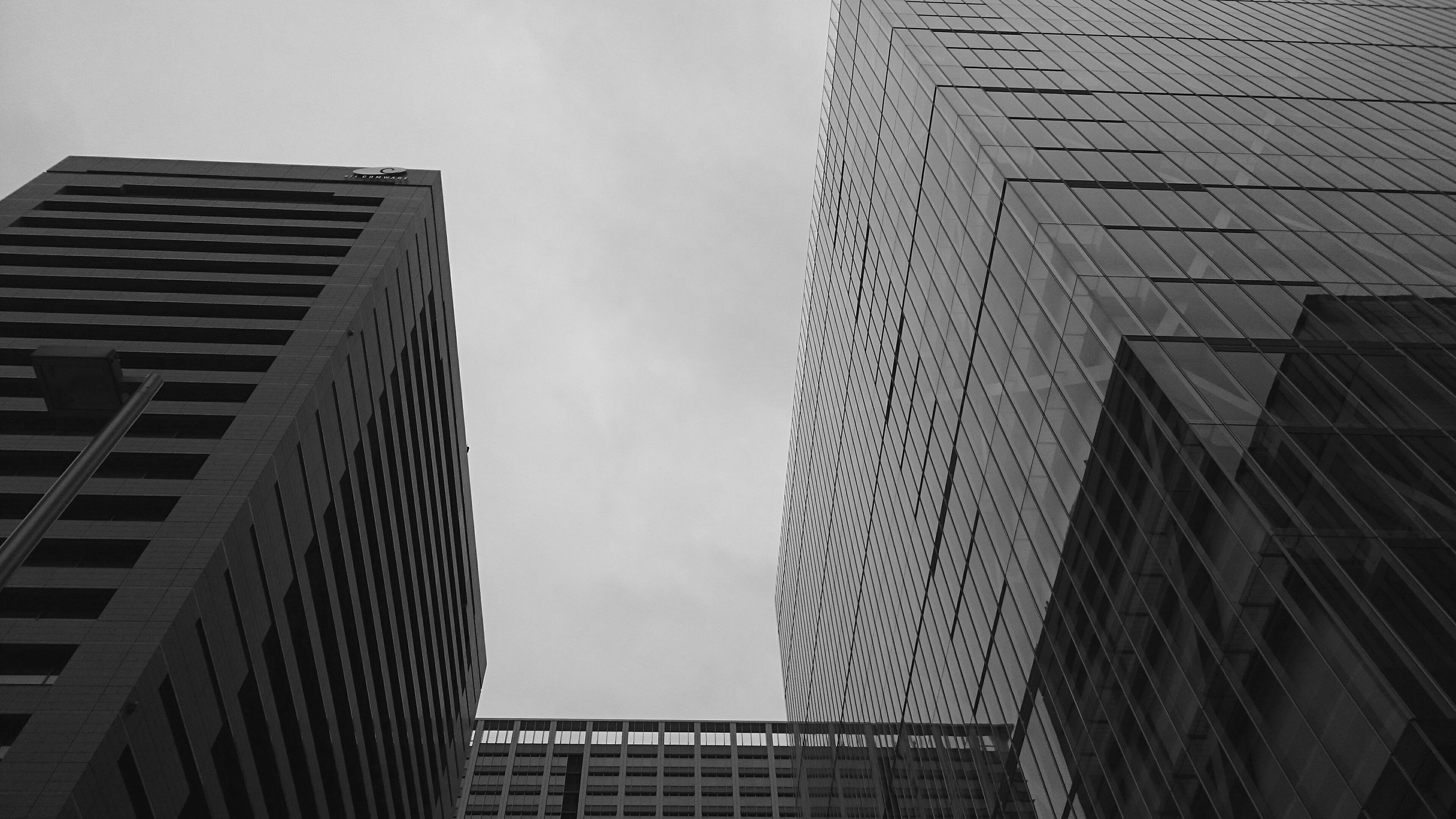 architecture, built structure, low angle view, building exterior, city, building, sky, office building, modern, tall - high, skyscraper, tower, outdoors, day, no people, window, glass - material, residential building, city life, directly below