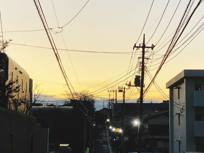 Low angle view of electricity pylon and buildings against sky during sunset
