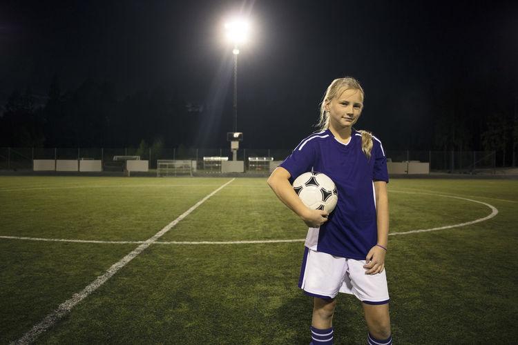Full length of boy holding ball on soccer field at night