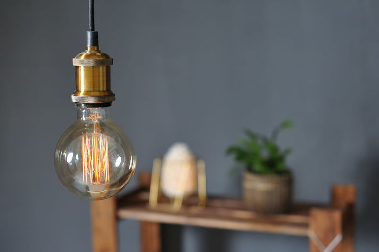 Close-up of light bulb on table at home