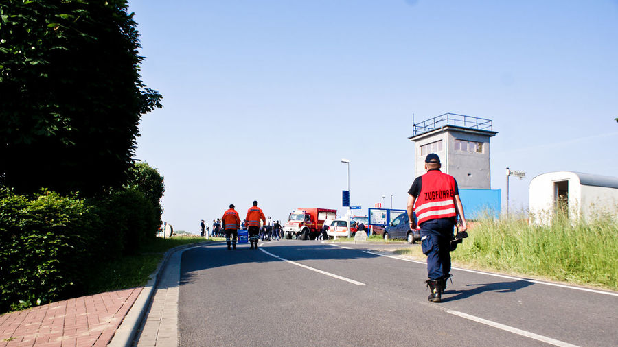 Rear view of male firefighters walking on road against sky