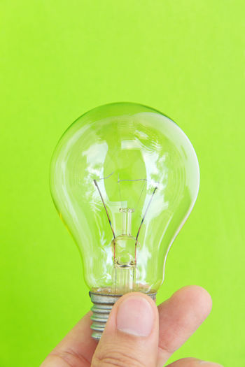 light blub in hand with green background, eco energy concept Earth Hour Green Color Close-up Colored Background Electricity  Electricity  Filament Holding Human Body Part Human Finger Human Hand Illuminated Light Bulb Lighting Equipment One Person People Power And Energy Save Energy Studio Shot Technology