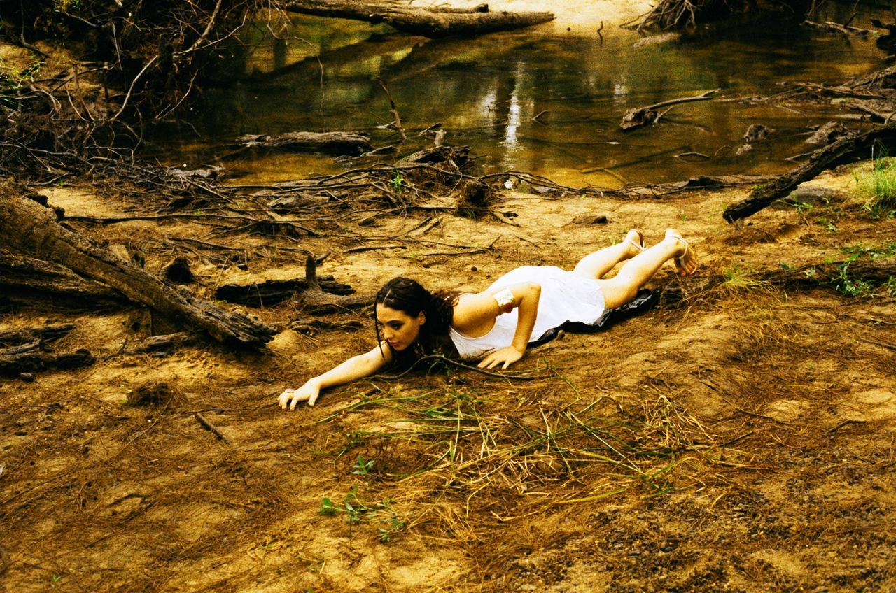 lying down, relaxation, full length, beautiful woman, one person, high angle view, young adult, water, beauty, real people, nature, day, outdoors, women, young women, lifestyles, beauty in nature, people