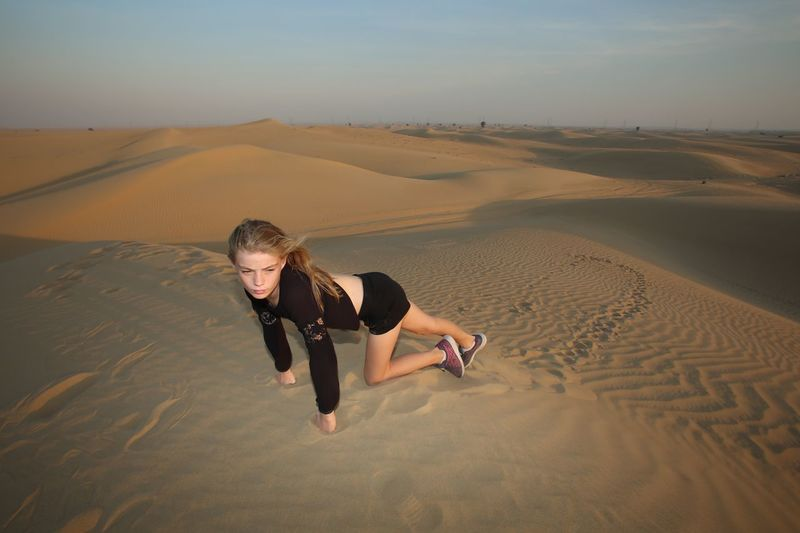 High angle view of girl looking away crawling on desert