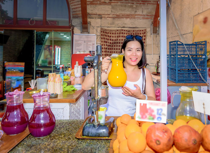 Portrait of smiling woman juice while standing in market
