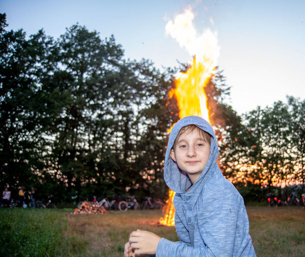 Portrait of cute boy wearing hooded shirt sitting against bonfire on field during sunset