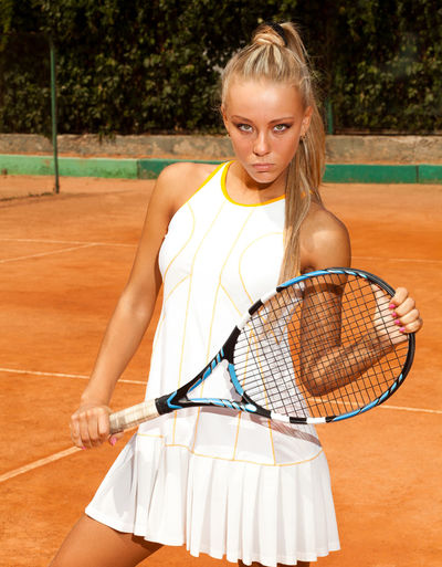 Nice woman in a tennis dress and with the racket in her hand standing on a sandy court Racket Tennis Racket Sport Tennis Leisure Activity One Person Real People Lifestyles Court Women Looking At Camera Portrait Clothing Blond Hair Standing Holding Young Adult Front View Hair Teenager Beautiful Woman Hairstyle