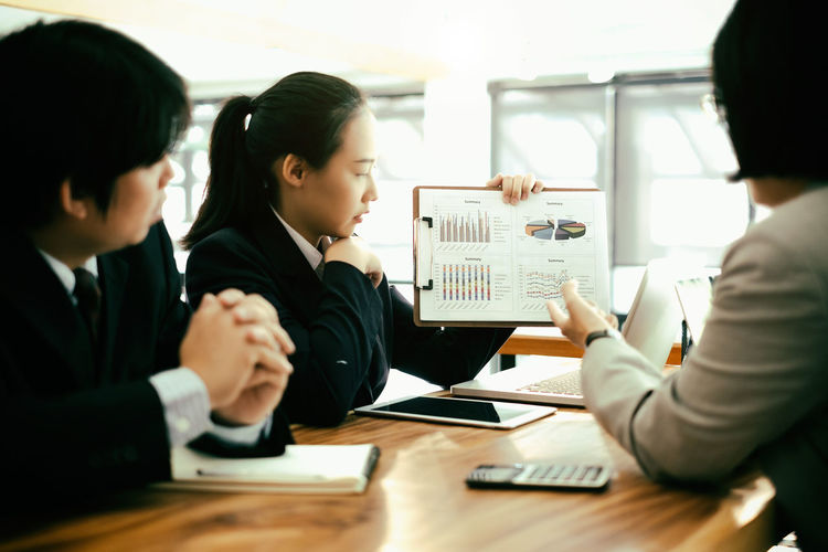Colleagues discussing over graph at desk in office