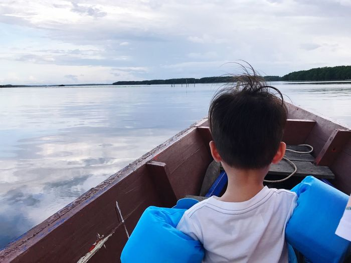 Rear view of boy sailing boat in sea against sky