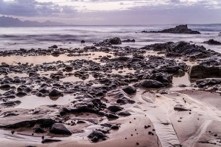 Aerial view of rocks on beach against sky