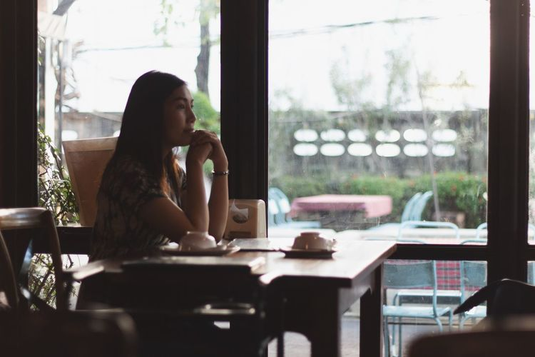 Side view of young woman looking away while sitting at table by window in cafe