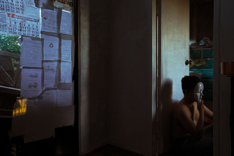 Rear view of shirtless man looking through window at home