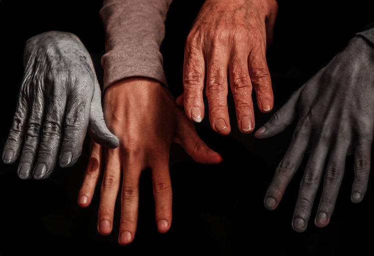 Close-up of cropped hands against black background