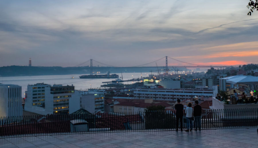Watching the sunset in Lisbon Bridge - Man Made Structure Cityscape Cityscape Cristo Rei (Portugal) Hanging Out With Friends Magic Hour Ponte 25 De Abril River River View Riverside Rooftop View  Rooftops Scenics Ship Sun Down Sunset Sunset Sky Tejo Travel Destinations Urban Skyline What A View