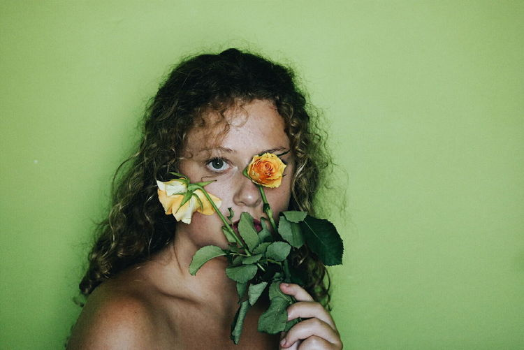 Portrait of shirtless young woman against green background