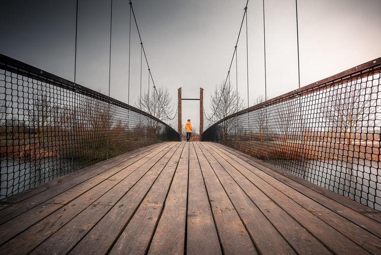 Rear view of person on footbridge against sky