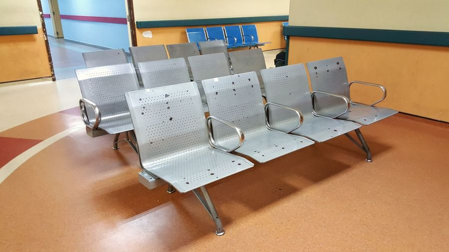 Empty Metallic Chairs In Hospital Waiting Room