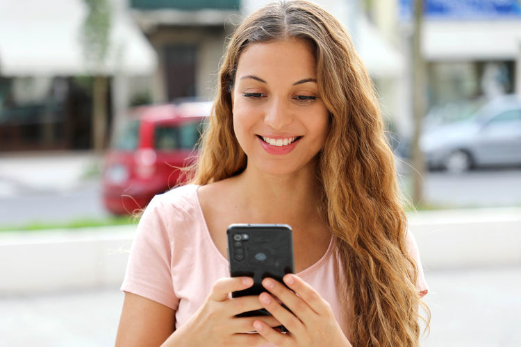 Smiling young woman using mobile phone in city