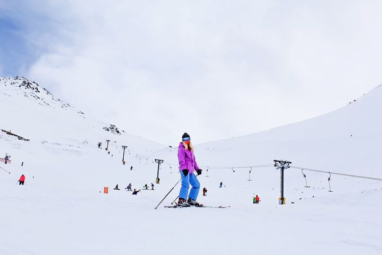 Woman Skiing On Snow Covered Field Against Sky