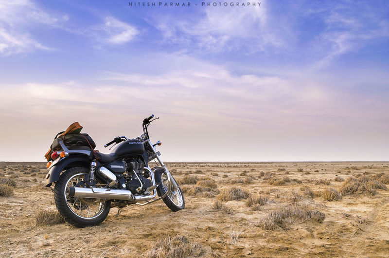 Man riding motorcycle on land against sky