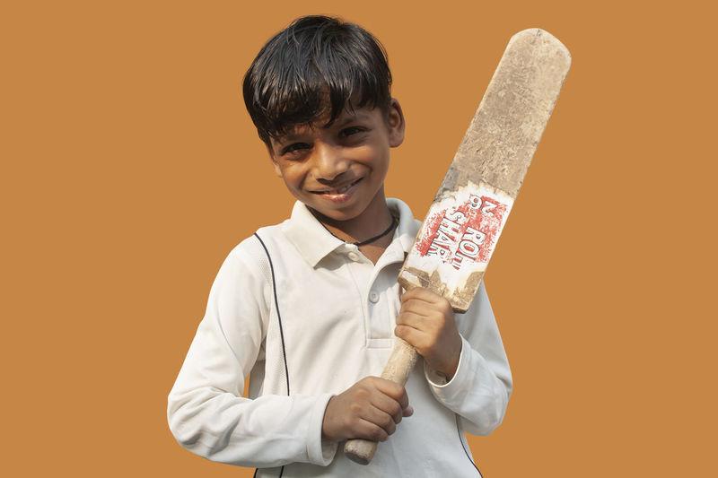 Portrait of smiling boy standing against orange background