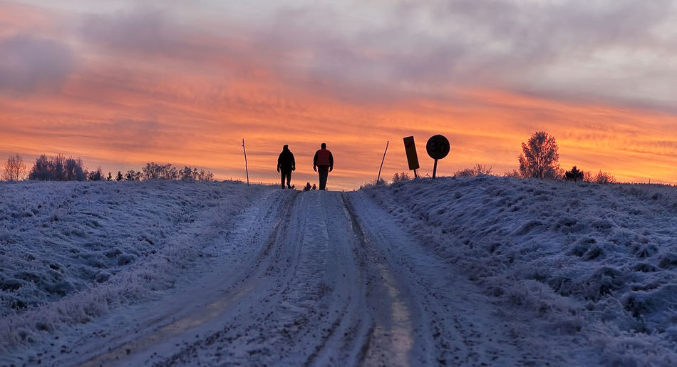 People on snow covered landscape against sky during sunset