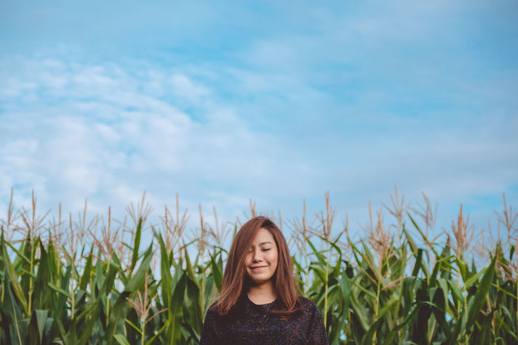Smiling beautiful woman standing at farm against sky