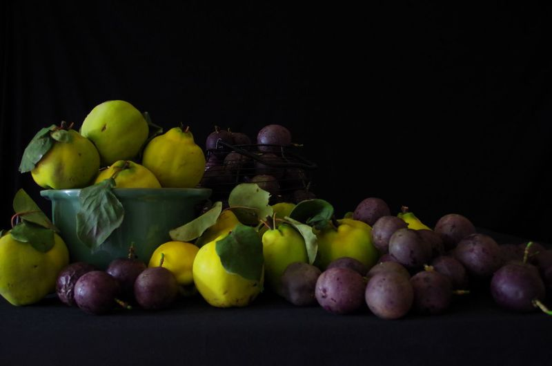 Close-up of grapes in container against black background