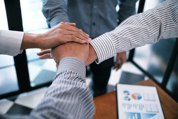 Colleagues stacking hands over graph in office