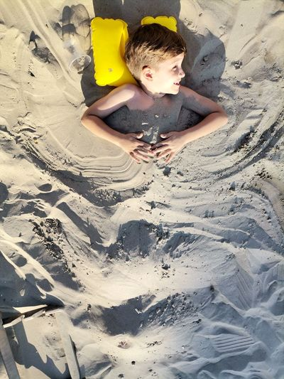 High angle view of boy playing on sand at beach