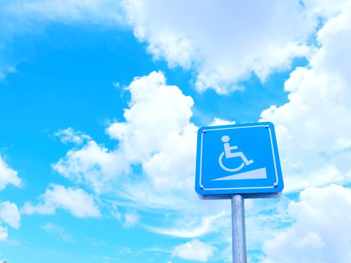 Low angle view of road sign against blue cloudy sky