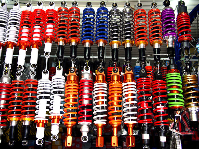 colorful motorcycle shock absorbers on display at a store Shock Absorber Shock Motorbike Motor Motorcycle Vehicle Transportation Coiled Spring Motor Vehicle Automobile Colors Colorful Metal Steel Iron Spare Part Suspension Multi Colored Choice Hanging Variation For Sale In A Row