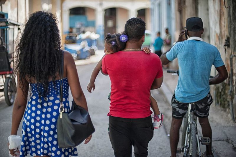 Baby Cuban Family Cyclist Adult Architecture Building Exterior Built Structure Casual Clothing City Day Friendship Leisure Activity Lifestyles Men Outdoors People Real People Rear View Standing Street Street Photography Togetherness Walking Women