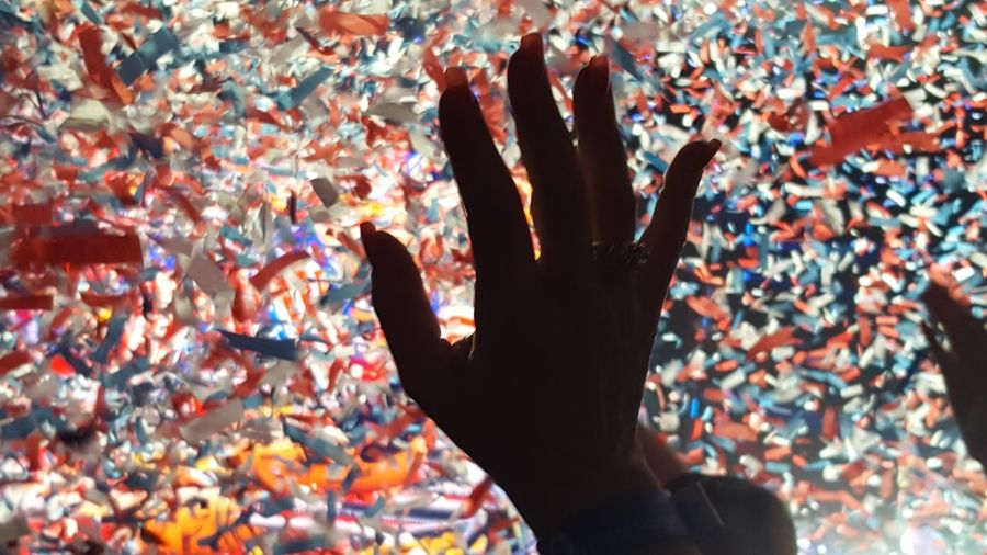 Cropped Hand Of Woman Against Confetti At Music Concert