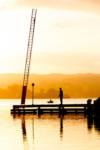 View to Dießen from Aidenried am Ammersee at sunset. Ammersee, Germany Pier Segeln Ammersee Beauty In Nature Bootsanleger Day Diving Platform Full Length Lake Men Nature Nautical Vessel One Person Outdoors People Real People Reflection Sailing Scenics Silhouette Sitting Sky Standing Sunset Tranquil Scene Tranquility Tree Water Waterfront