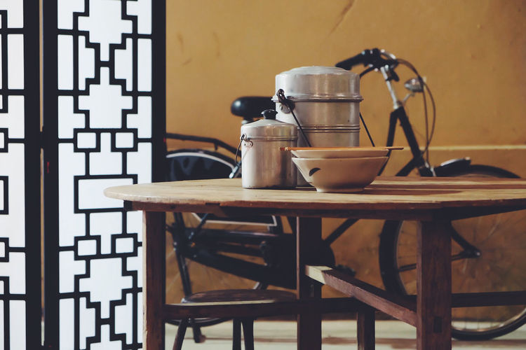 Close-up of containers on table and bicycle against wall