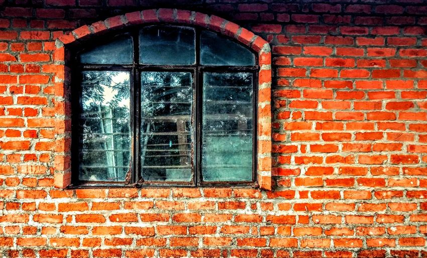 Full frame shot of window on red brick wall