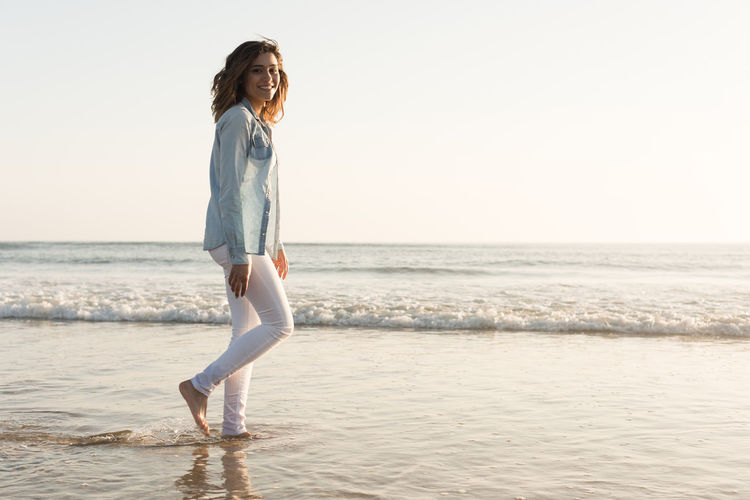 Full length portrait of woman walking at beach against sky during sunset