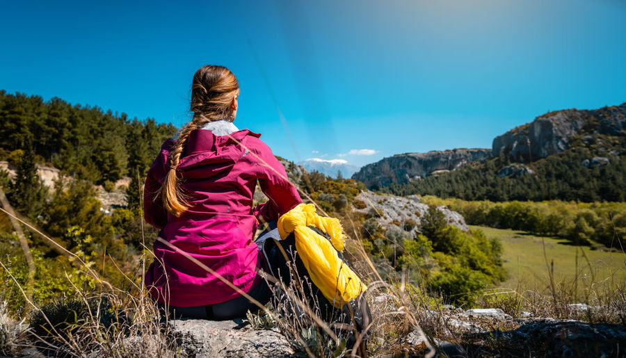 Woman making rest from hiking watching the hills, nature, and beautiful scenery in spring